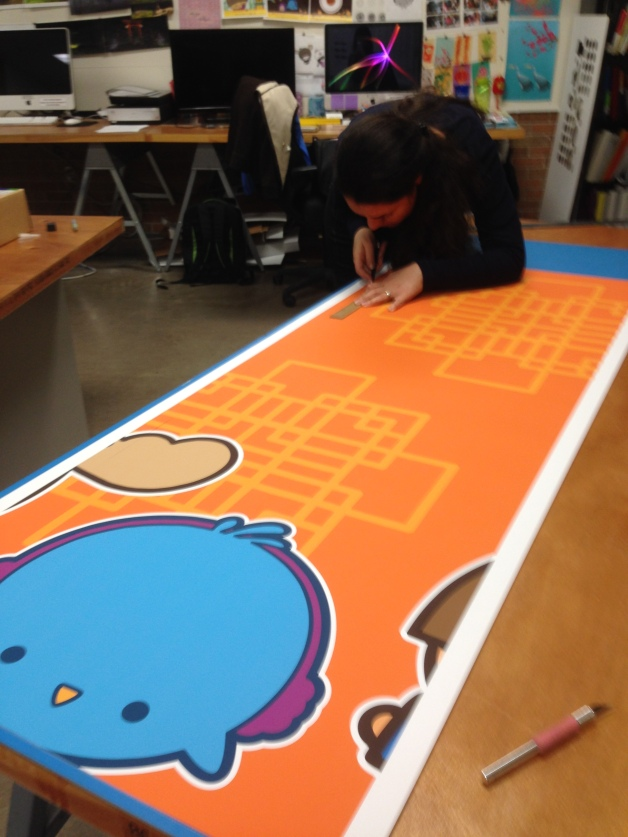 part of a poster series to be placed on the wall; my colleague Maryam helping to trim the posters to edge